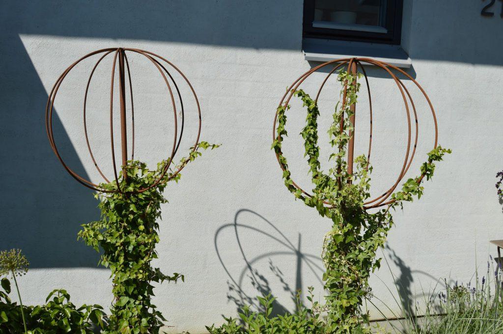 Detalj, klatreplanter i rustne klatrestativer. Trädgårdsrundorna