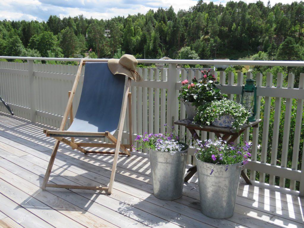 Deilig fluktstol med solhatten klar ved siden av et stilleben av sommerblomster