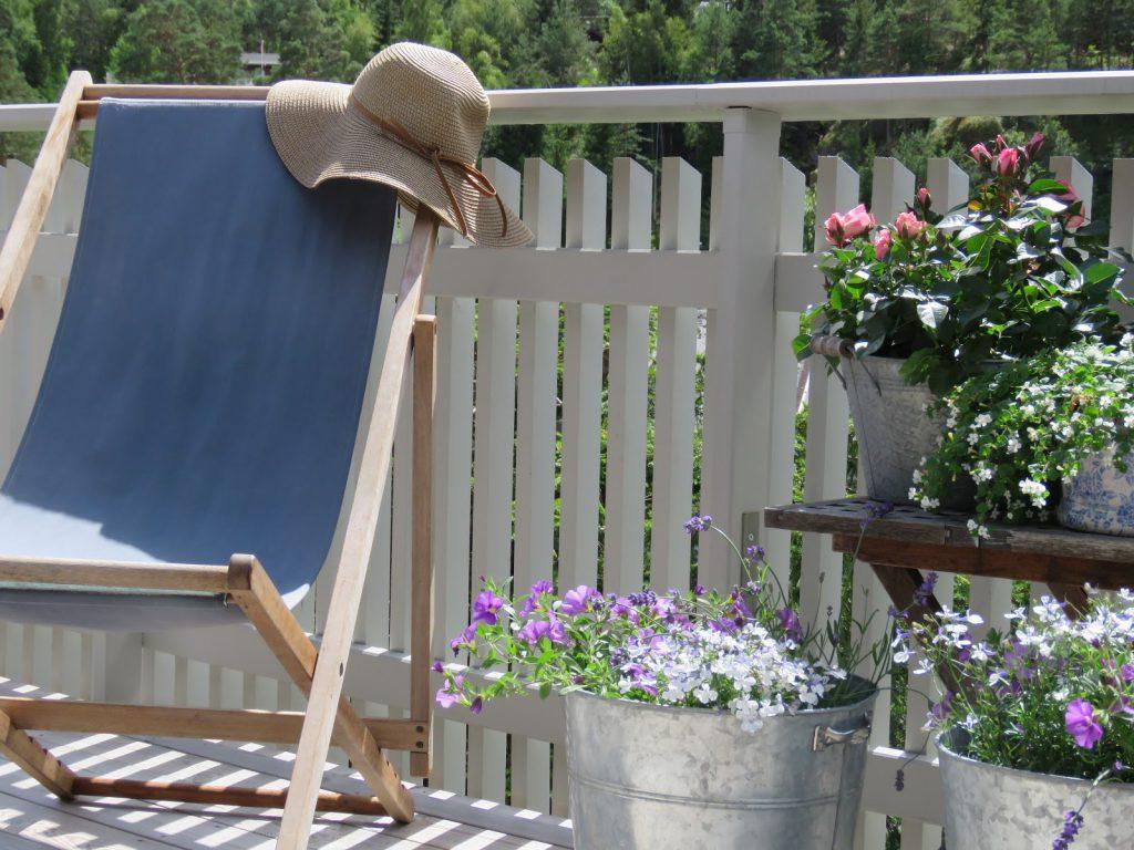 Å rive og bygge hytteveranda  blir det mye kos av - Stilleben av fluktstol og sommerblomster på hytteverandaen