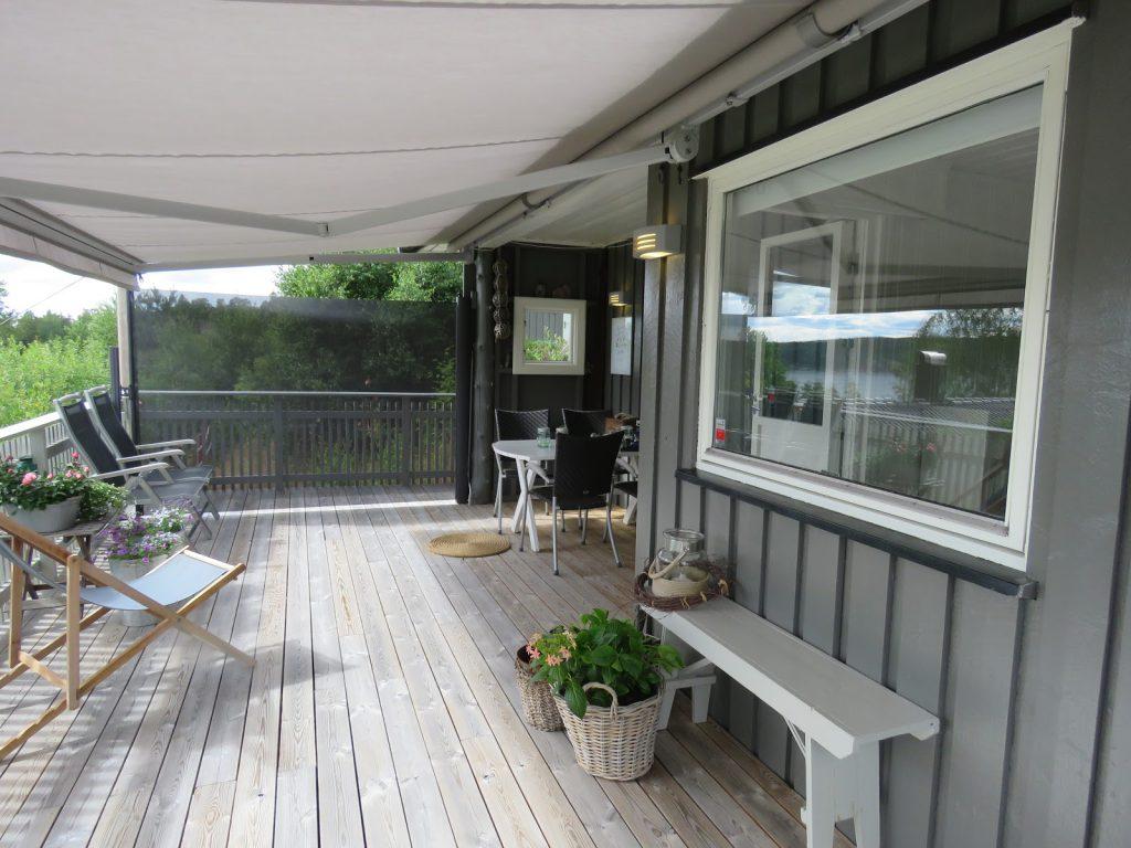 Hytteverandaen med utslått markise og vindskjerm
