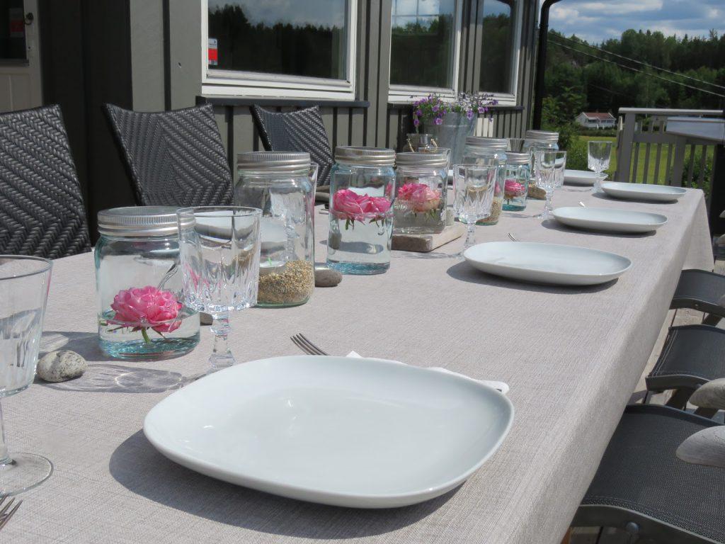 Bordet på hytteverandaen er dekket til sommergjester med blant annet roser i Norgesglass