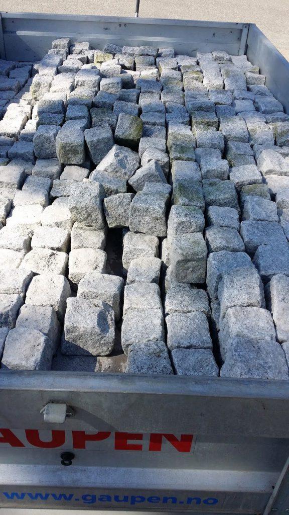 En sirkel av brostein blir til i Furulunden, 650 brostein i tilhengeren.
