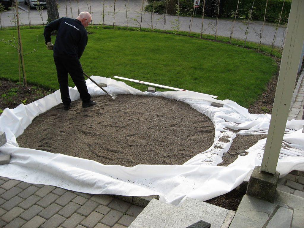 En sirkel av brostein blir til i Furulunden, tykk duk, pukk og singel er på plass.