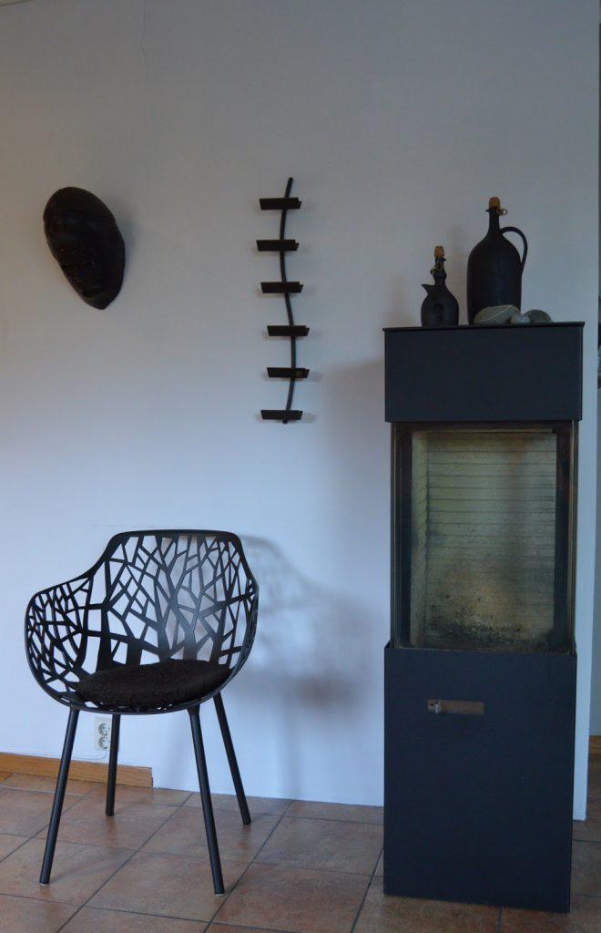 Tidløst design i interiøret. Peis og designstol og dekorasjoner på veggen, et stilleben. Furulunden