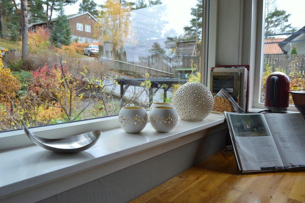 Kjøkkenbenk med stilleben i vinduskarmen.