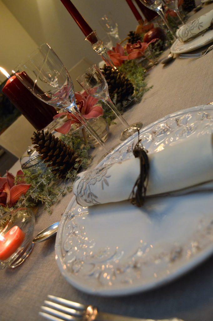 Borddekking med dyprøde lys og orkideer til jul. Nærbilde av serviettringer. Furulunden DSC_0094