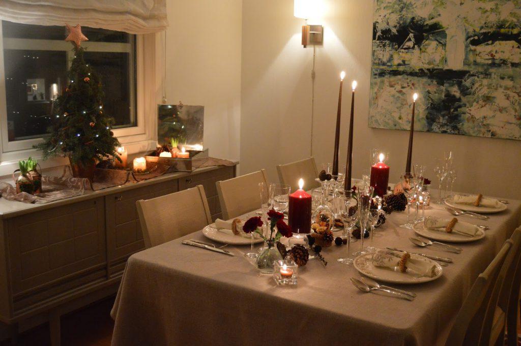 Borddekking med dyprøde blomster og kongler til jul. Ferdig pyntet og med servise på. Furulunden