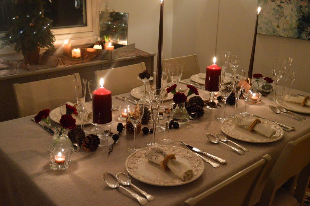 Borddekking med dyprøde blomster og kongler til jul, ferdig dekket bord. Furulunden