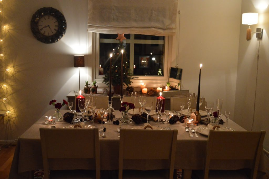 Borddekking med dyprøde blomster og kongler til jul. Ferdig dekket bord og med lysene tent. Furrlunden