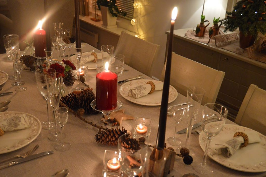 Borddekking med dyprøde blomster og kongler til jul. Flere detaljer fra et dekket julebord. Furulunden