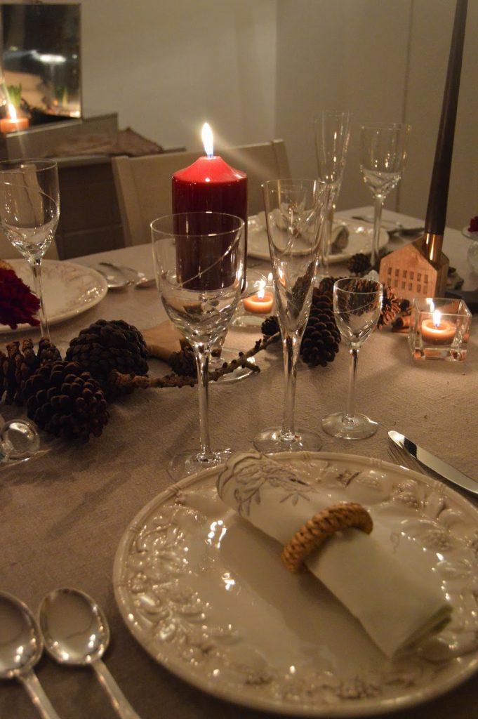 Borddekking med dyprøde blomster og kongler til jul. Detaljer fra et dekket julebord. Furulunden