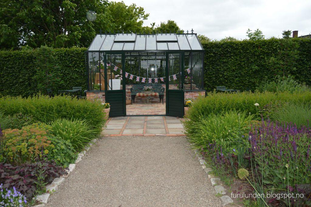 Historikk og oppskrift på en cottage garden. Drivhus vel plassert midt mellom blomsterbedene