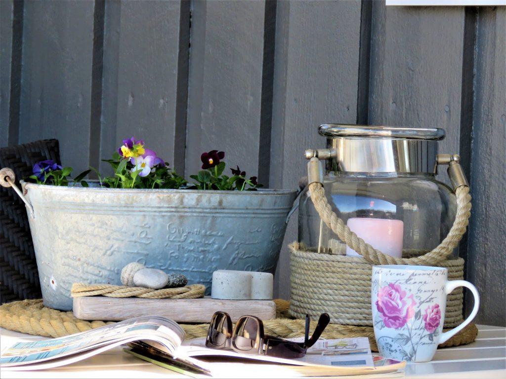 Vårblomster i krukker har ankommet hytta - Vårblomster - sittegruppe på veranda - under tak - hytta