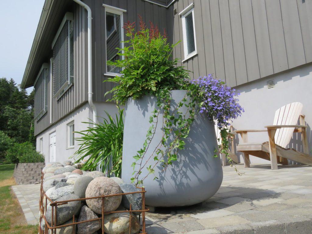 En sjarmerende uteplass med gabionmur og blomsterkrukker. Hos Signe Kari og Vidar