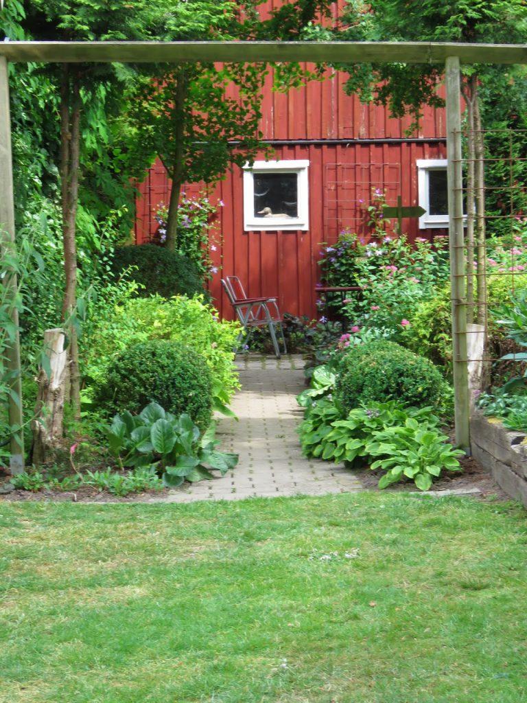 Blomsterbed som ender opp ved en bygning i Lotties Trädgård. Trädgårdsrundorna i Helsingborg.