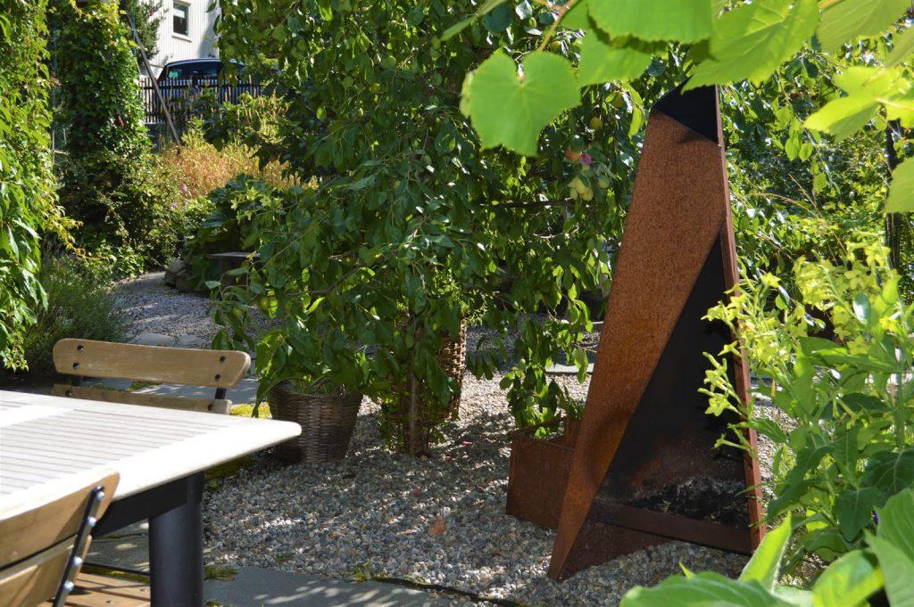 Se en hage i harmoni med seg selv - Rusten peis ved spiseplassen. Furulunden.