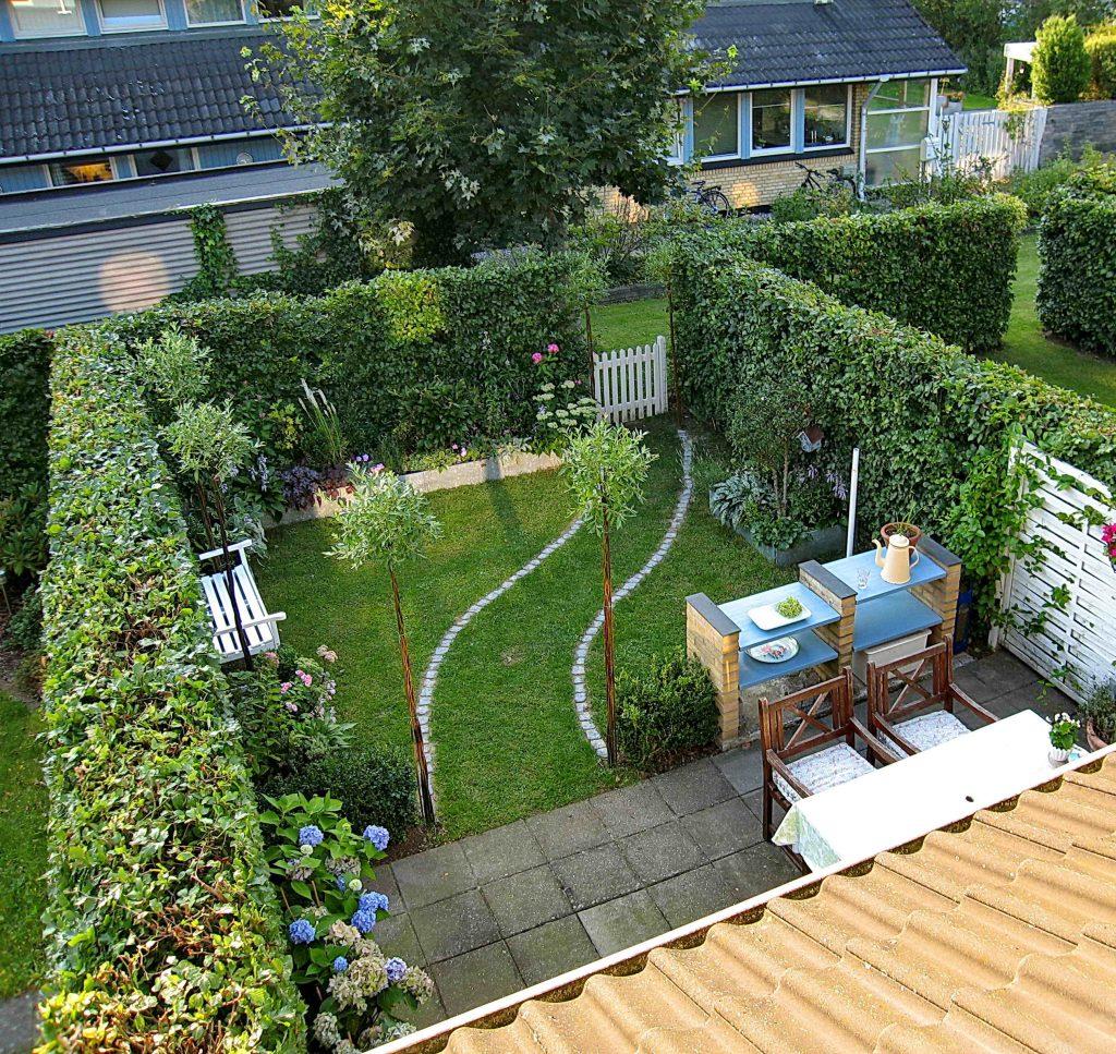 En liten rekkehushage med terrasse og gressplen