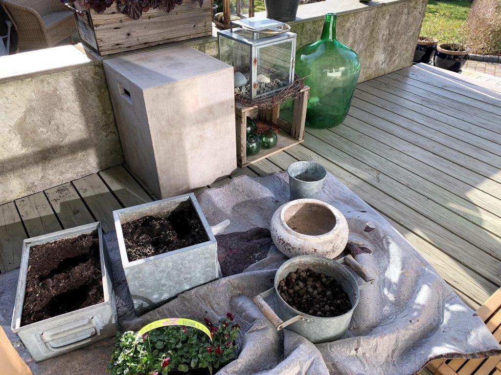 Klargjøring av krukker og kar til et vårlig arrangement på terrassen