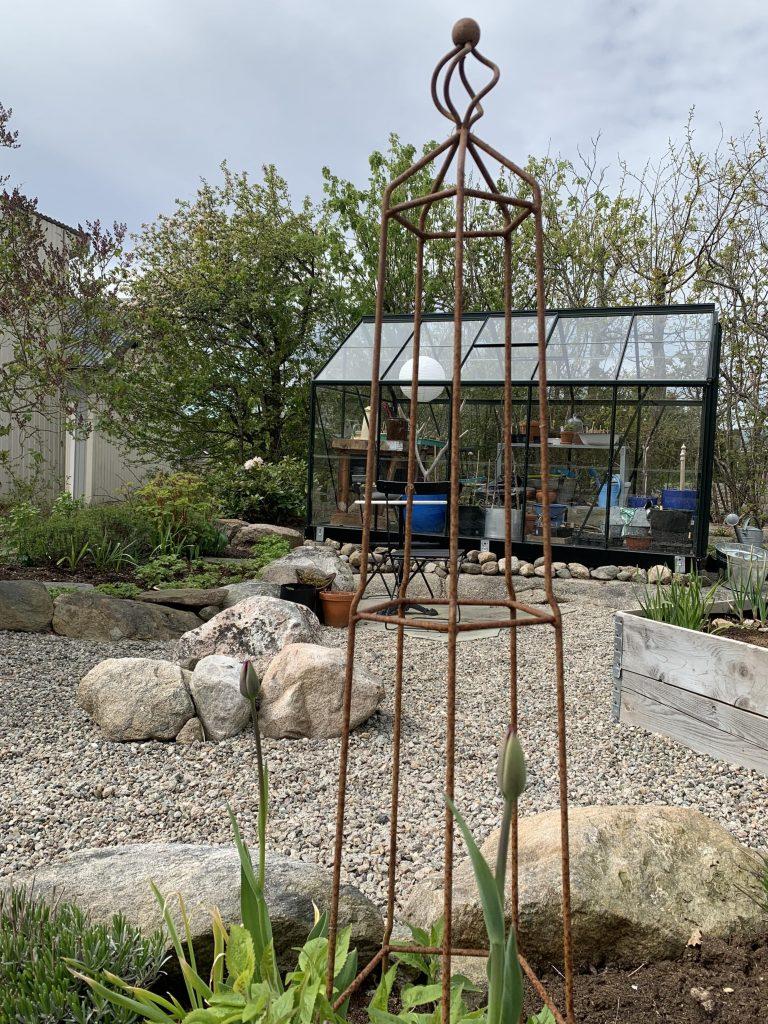En hage med fjellknauser - drivhuset sett på avstand