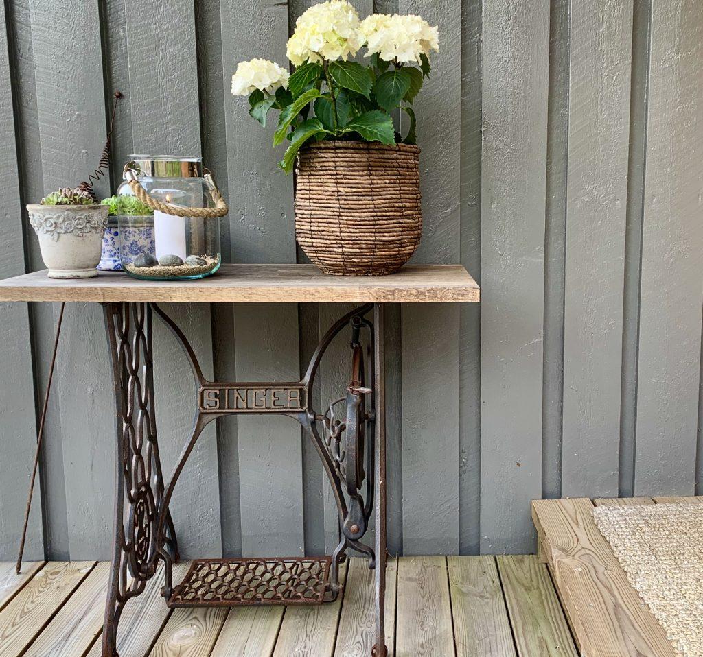 Et gammel Singer symaskinbord gjør nytte til blomsterbord ved inngangspartiet -