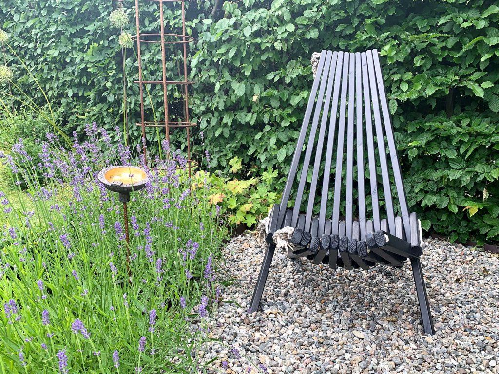 En sitteplass i hagen rammet inn av Lavendel