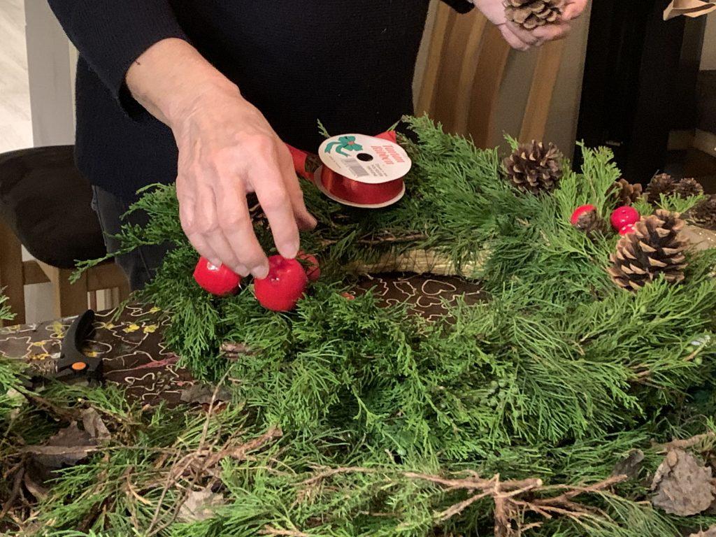 En av venninnene prøver ut dekoren til julekransen
