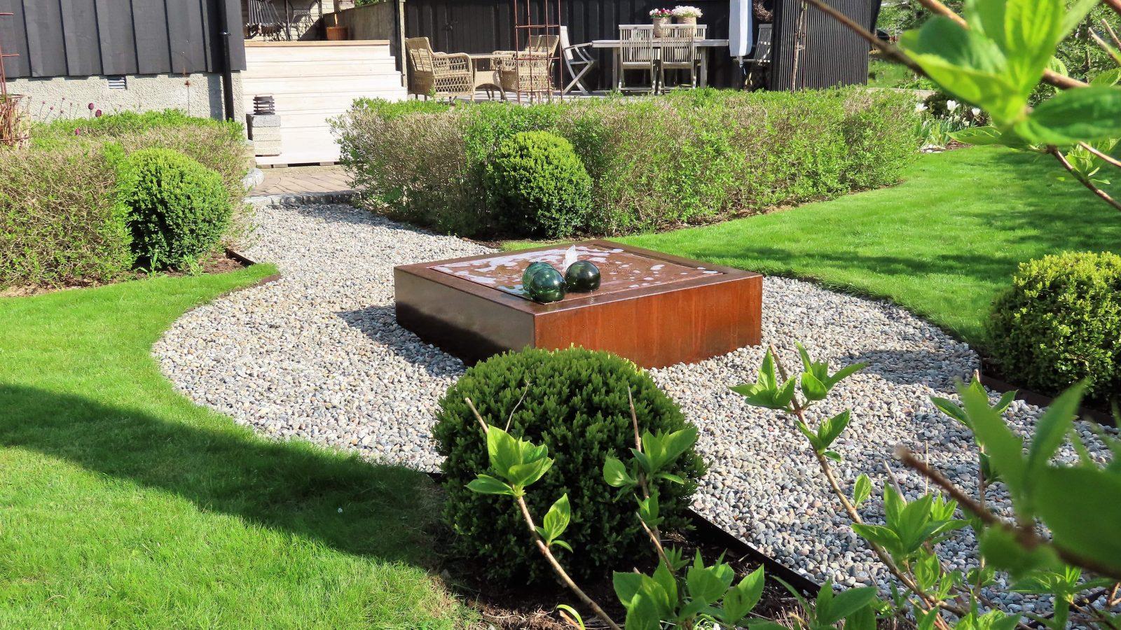 Vår i hagen med blomstring og rislende vannfontene - Fontenen-