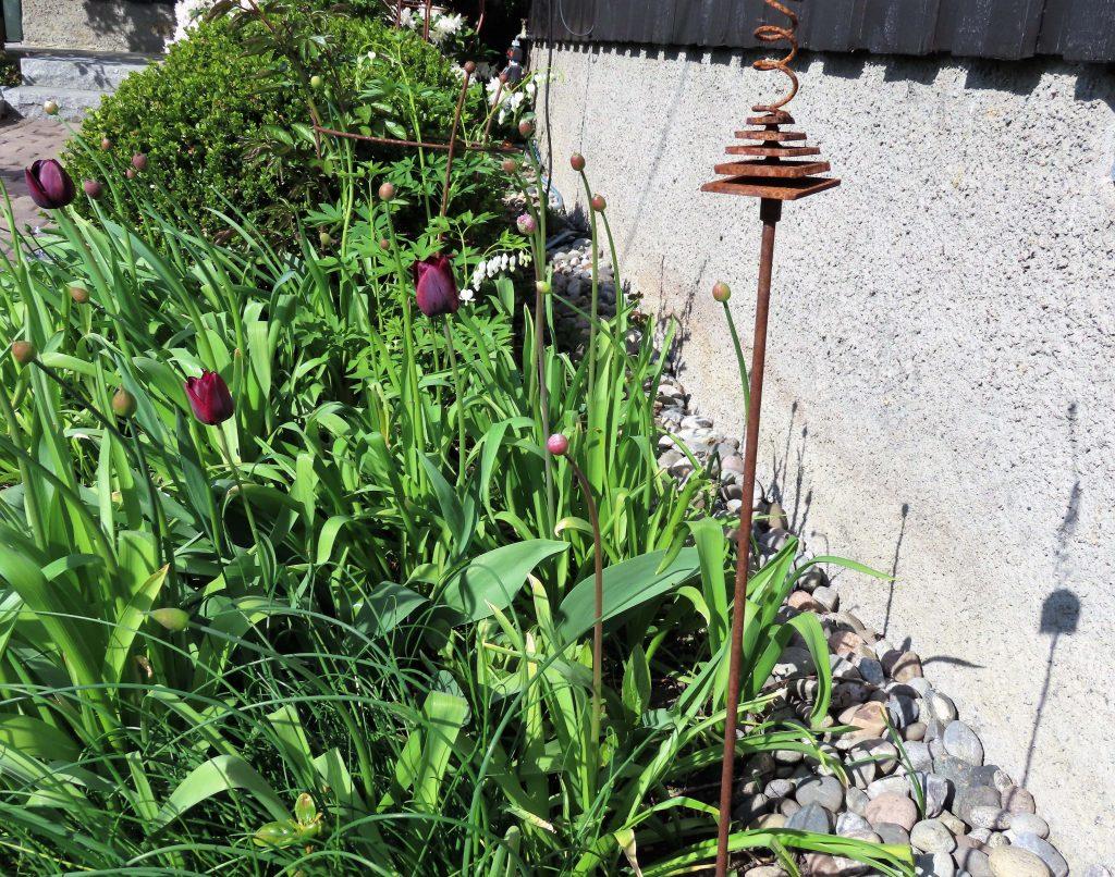 Vår i hagen med blomstring og rislende vannfontene - blomstring under stuevinduet